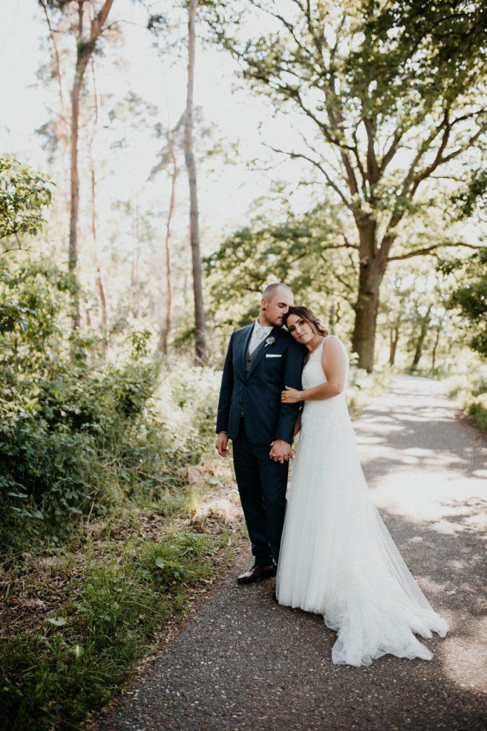 Brautpaar steht auf Weg, Braut lehnt sich ans eine Schulter an