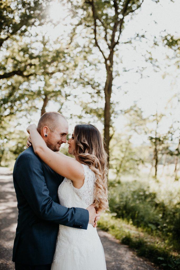 Braut schlingt Arme um Hals von Bräutigam